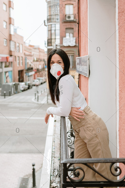 Side view of young female in casual outfit and protective mask standing on balcony in city and looking at camera while spending day in self isolation at home during coronavirus pandemic