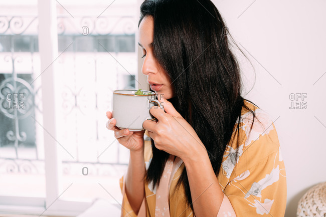 Calm relaxed brunette woman in home clothes holding mug of hot tasty tea and blowing before drinking while enjoying free time at home