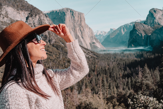 Full body side view of happy relaxed young female traveler in stylish outfit sitting on stone border against picturesque mountain scenery with rocky cliffs and coniferous forest in Yosemite National Park in USA
