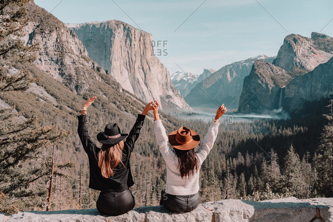 Back view of happy unrecognizable female friends in trendy clothes and hats sitting on edge of rocky cliff and enjoying amazing mountain scenery while visiting Yosemite National Park in California in sunny spring day