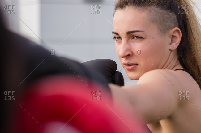 Female fighter in boxing gloves training punches during workout in city