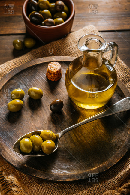 From above glass jar with extra virgin oil placed on wooden plate with black and green olives