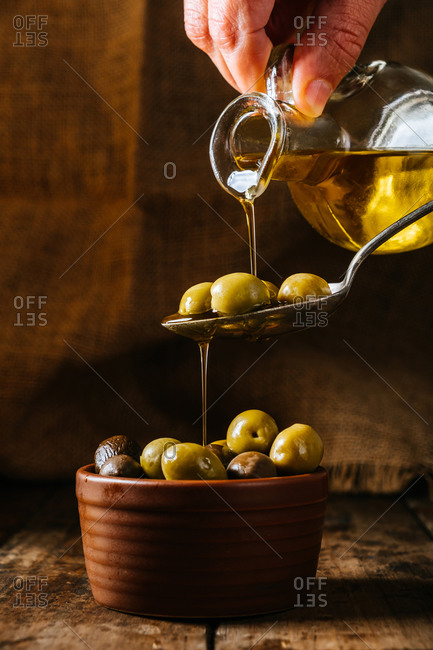 Cropped unrecognizable person pouring oil in spoon and ceramic bowl with olives placed on wooden table in kitchen
