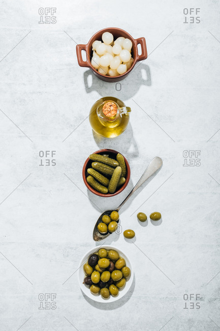 Top view of bowl with pickled cucumbers and plate with olives placed on table in row along with glass oil jug