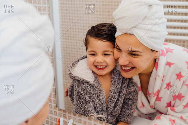 Cheerful woman with towel turban cuddling little child in bathrobe after taking shower and looking in the mirror