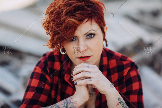 Independent stylish young female with trendy haircut and tattoos wearing casual checkered shirt looking at camera while standing against blurred shabby building
