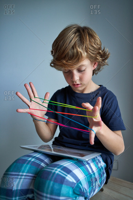 Concentrated preteen boy in pajama sitting on wooden stool with tablet on knees and creating string figure while playing creative cats cradle game at home