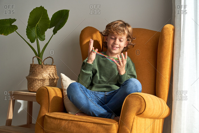 Cheerful preteen boy in casual clothes sitting in cozy armchair and playing interesting cats cradle game while resting at home