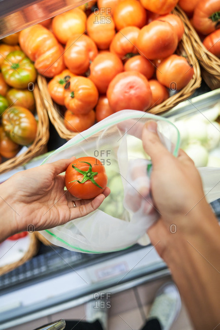 Female hand picking up tomato with recyclable bag