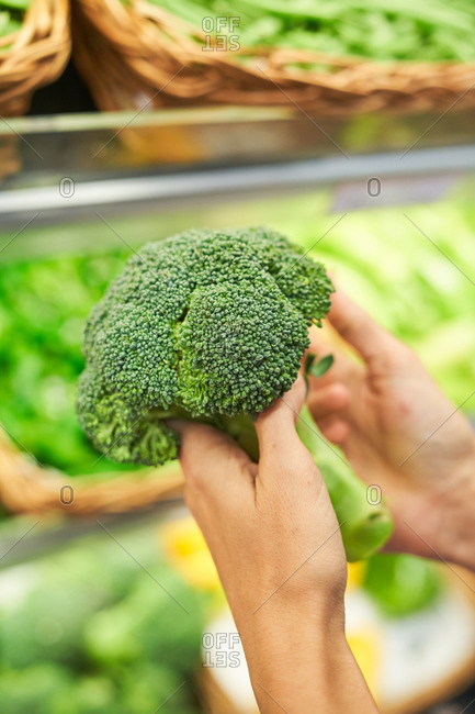 Female hand with broccoli in her hand in a fruit shop