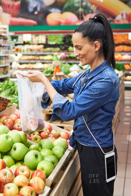 Girl buying fruit and vegetables using recyclable bags