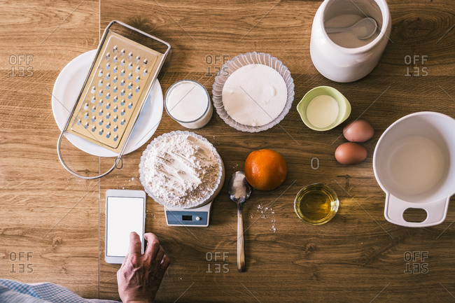 Top view of crop anonymous female browsing recipe on smartphone and weighing wheat flour on electronic scales while preparing ingredients for homemade pastry in kitchen