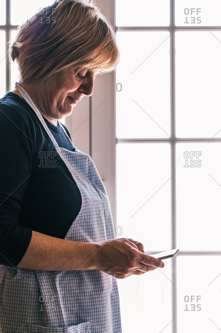 Side view of smiling senior female in apron browsing smartphone and searching for recipe while standing in light home kitchen