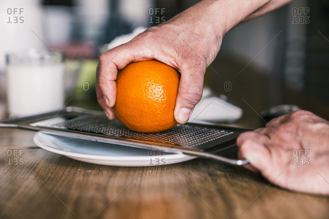 Side view of crop anonymous woman removing orange zest with grater while preparing aromatic pastry in home kitchen