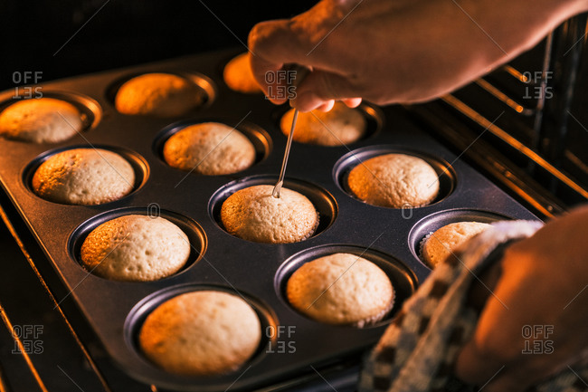 Crop confectioner checking dough in muffins with metal stick while cooking delicious homemade dessert in kitchen