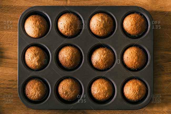 Top view of delicious muffin in paper case on tray placed on wooden table in kitchen