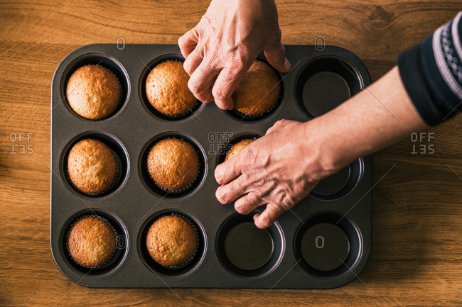 Top view of anonymous senior cook taking delicious muffin in paper case from tray placed on wooden table in kitchen