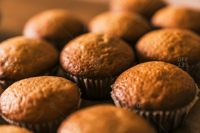 From above close up of delicious ready to eat muffin in paper case placed on wooden table in kitchen