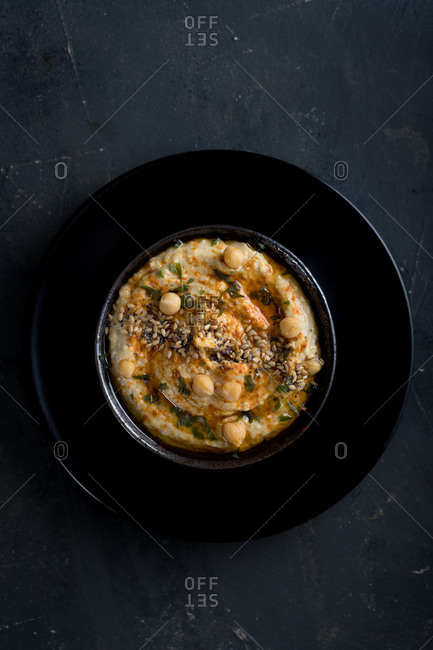 Top view of Delicious homemade hummus with paprika, seeds and olive oil
