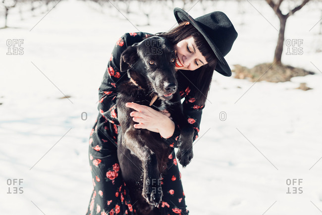 Smiling young fashionable brunette female in black hat and dress and beautiful black dog looking at camera in snowy field with leafless trees in sunny winter day