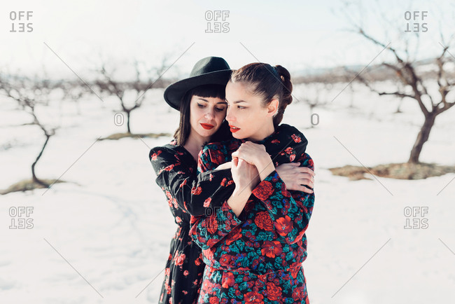 Young sensual affectionate ladies in colorful trendy outfit embracing while standing in snowy park in sunny winter day