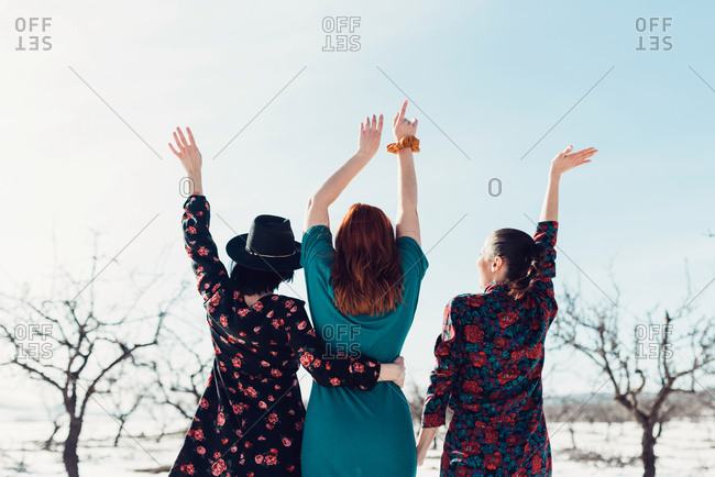 Cheerful young girlfriends in colorful dresses having fun and standing on snow in winter field with tree plantation