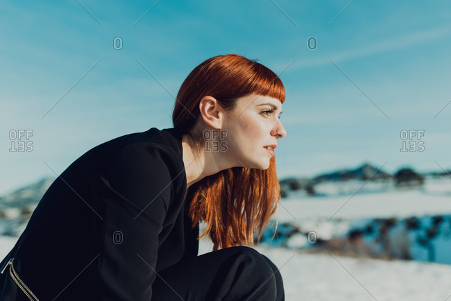 Red haired female in black suit over naked breast sitting against snowy field in sunny winter day