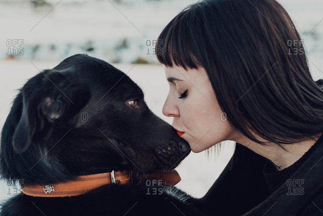 Side view of young brunette female with eyes closed kissing in nose adorable black dog
