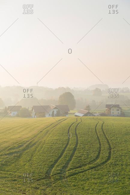 Scenery view of vast field with furrows located near village houses under hill in daylight in countryside with fog far away