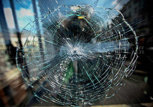 Window with damage effect as net of circles and lines of cracks on translucent glass surface