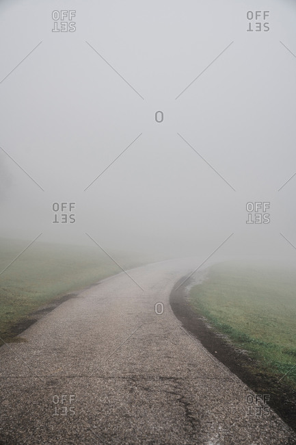 Narrow empty winding asphalt road with cracks and trees on green meadow with road sign under fog in daytime in countryside