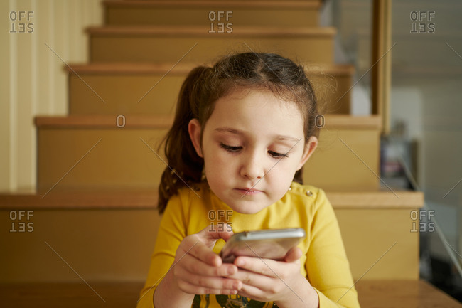 Calm small girl in casual yellow clothes focusing on screen with interest and interacting with smartphone while sitting alone on stairs in corridor of country house