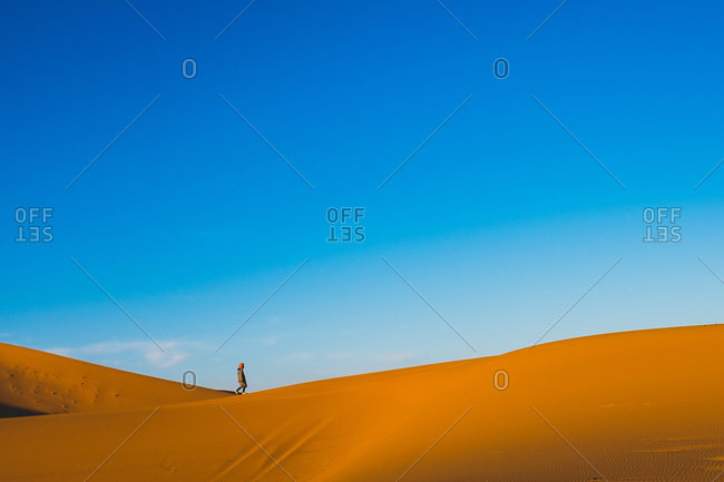 Side view of amazing landscape of desert with lonely tourist strolling along sand dune during sunset in Morocco