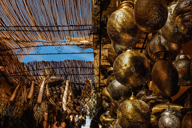 Low angle of Moroccan local bazaar with traditional hanging lamps and dry plants for sale