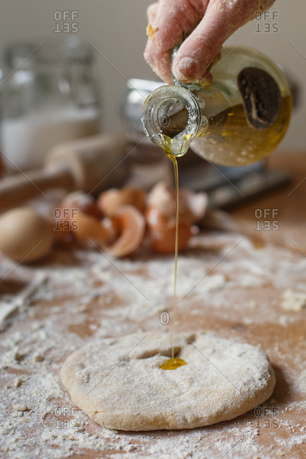 Faceless cook pouring fragrant fresh olive oil from glass jug onto rolled pasta dough on background of blurred kitchen mess