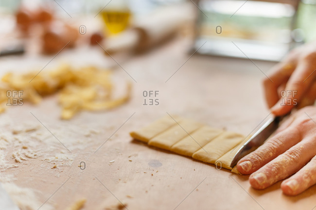 Faceless cook cutting dough into thin strips by knife on wooden table sprinkled with flour while preparing pasta in daytime