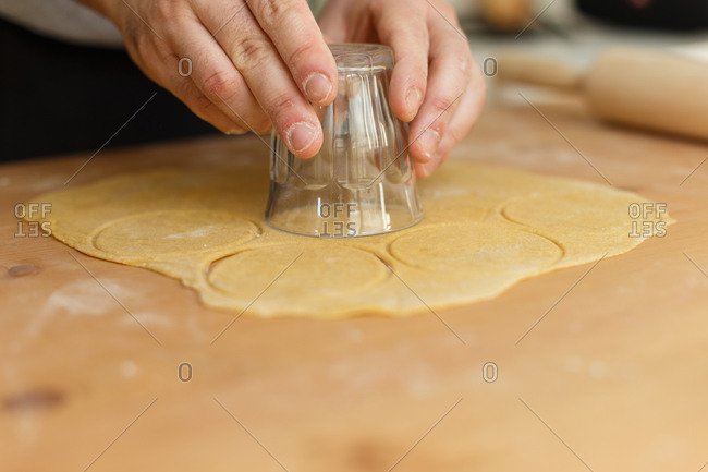 From above of unrecognizable male cooking ravioli on wooden table with rolling pin and cutting circle by glass from rolled dough