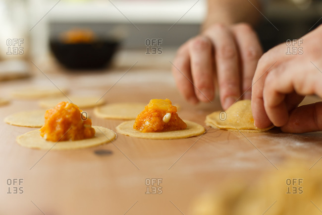 Faceless cook pressing edges of pumpkin ravioli with fingers on table while preparing gourmet dish in cozy home kitchen in daylight