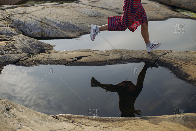 Side view of anonymous crop female traveler in white sneakers and skirt running between puddles on rocky ground on sunny day