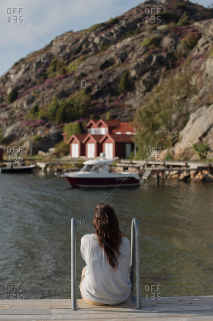 Back view of anonymous female tourist in casual warm clothes sitting on wooden boardwalk and admiring calm view of boat and houses