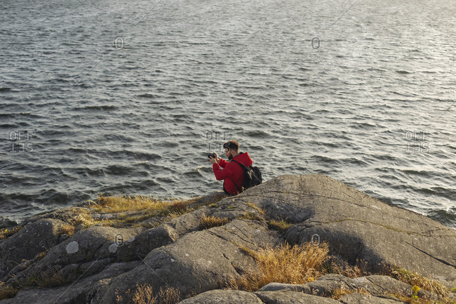 Male tourist in casual red jacket and with backpack sitting on rocky cliff and taking pictures of beautiful seascape