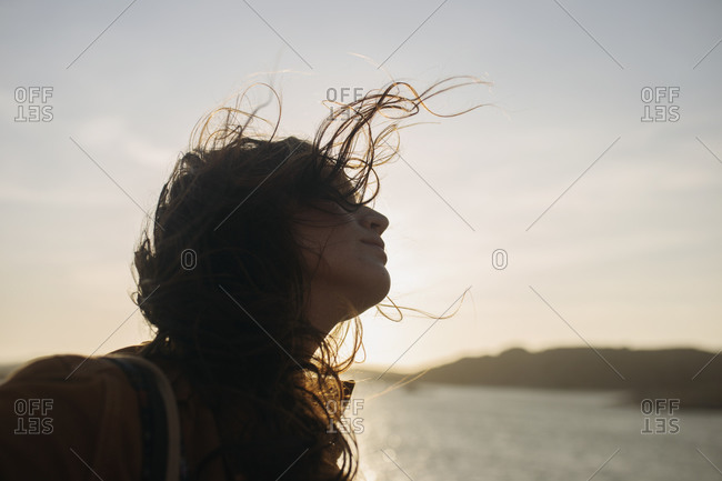 Side view of female wearing casual clothes standing on quay and enjoying breeze on sunny day and looking away