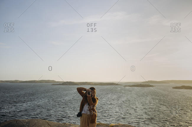 Anonymous female tourist in casual clothes standing on rocky cliff on seashore and taking photos while enjoying amazing seascape during vacation