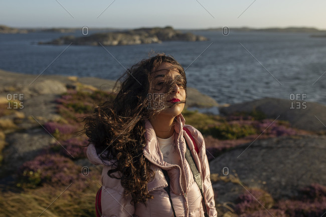 Side view of female wearing casual clothes standing on lake shore and enjoying breeze on sunny day and looking at camera