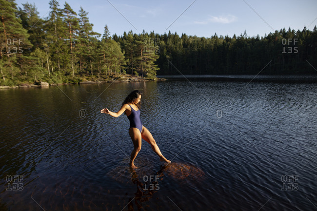 From above side view of slim female in swimsuit standing in calm water of lake while enjoying sunset and majestic scenery