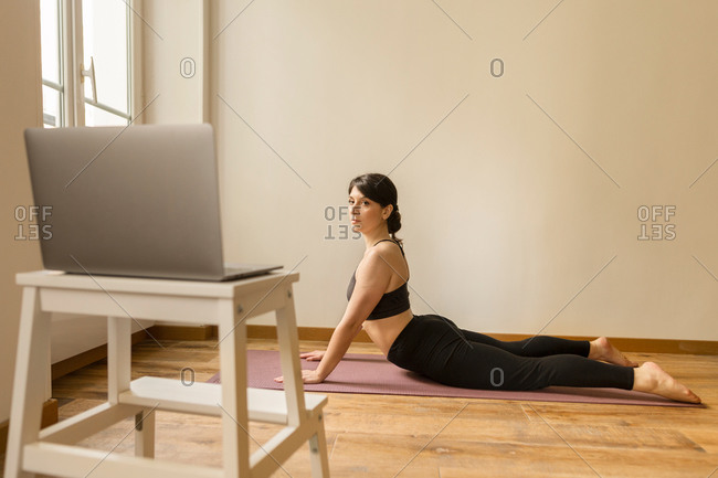 Side view of flexible female watching exercises on laptop and practicing yoga in Cobra pose on mat