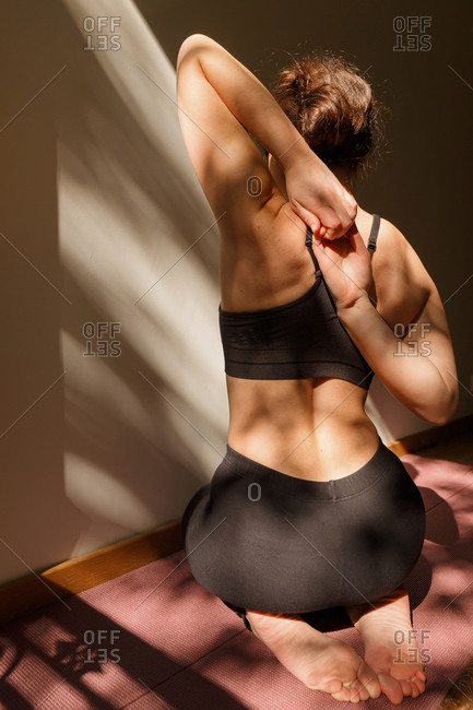 Back view of anonymous slim female in sport clothes sitting on mat in gomukhasana pose at home on sunny day