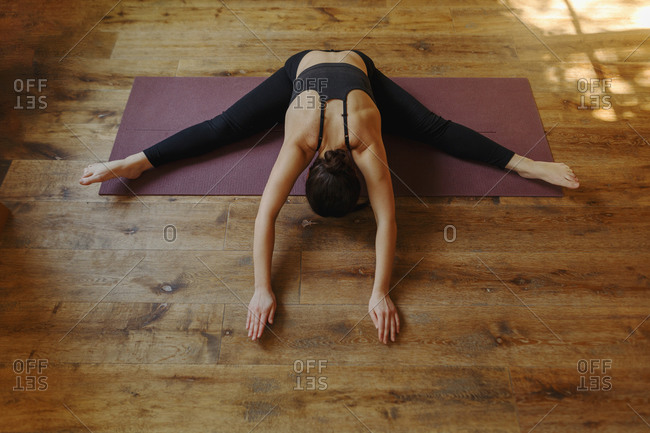 From above of anonymous sportive lady sitting in wide legged forward bend pose on mat while practicing yoga in flat in afternoon and touching wooden floor