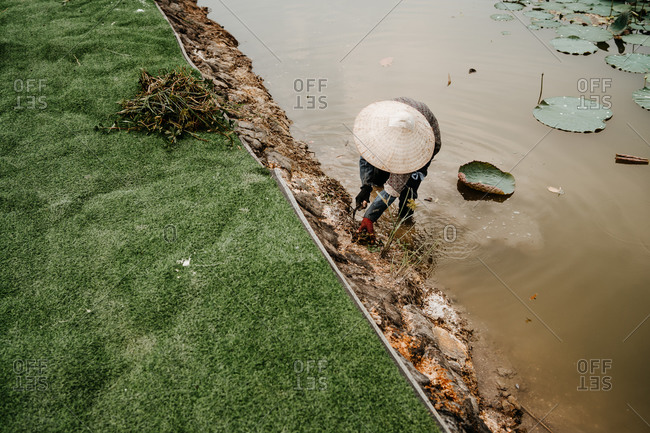 High angle of unrecognizable busy farmer wearing straw hat standing in water of dirty river and cultivating soil with hoe