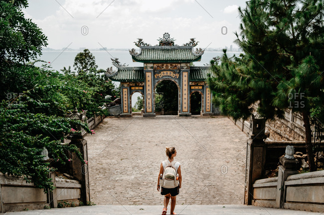 Back view of anonymous female tourist with backpack standing on stairs in front of arch of Buddhist temple in Vietnam